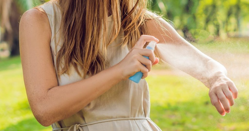 Woman spraying essential oil for insect repellent